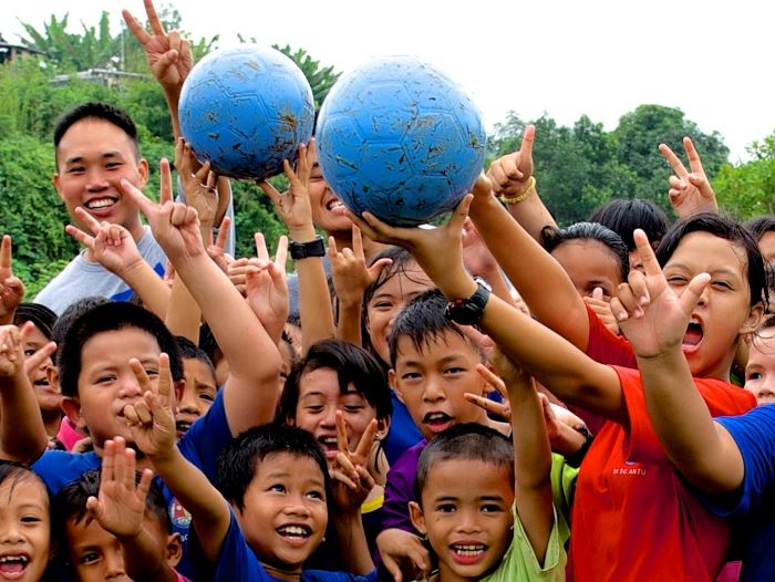 Children playing with blue balls received from one world play