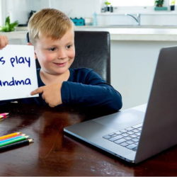 Boy showing sign to computer that says let's play grandma